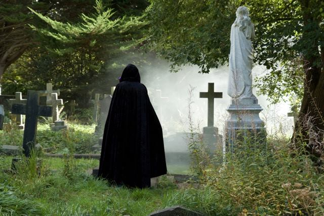 cloaked figure standing in a misty cemetery amongst gravestones