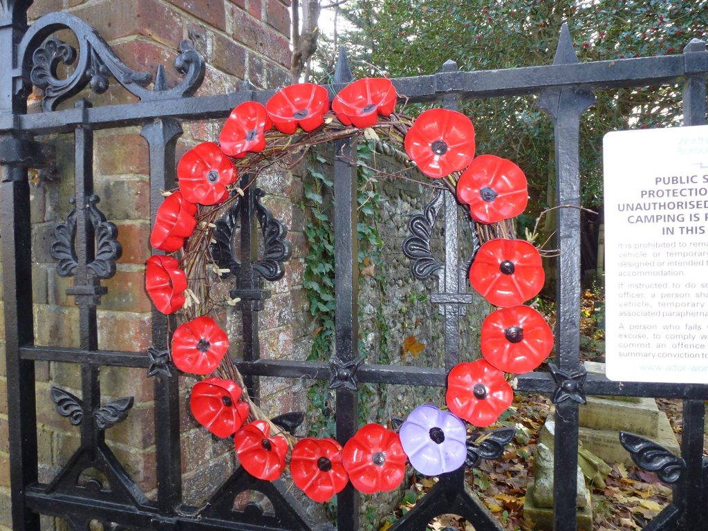 Red poppy wreath on black iron gates to cemetery