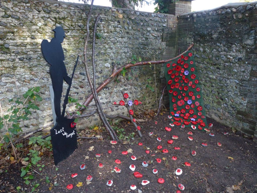 handmade poppies resembling stream coming out of a wall in corner of cemetery next to silhouette of soldier with rifle.