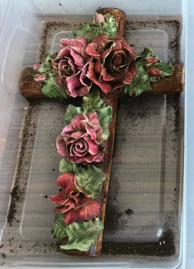 a brown cross covered with ornate ceramic roses